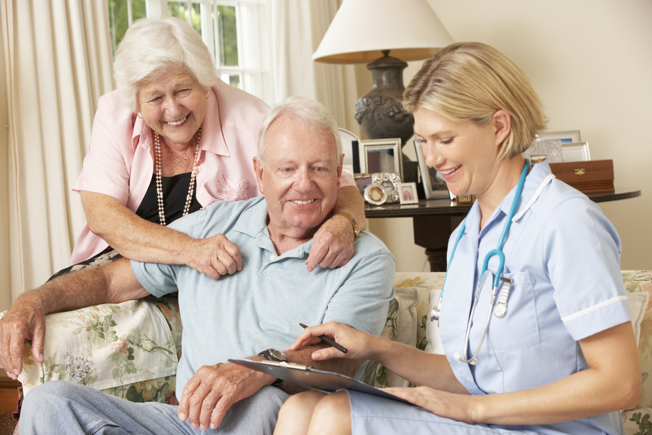 Retired Senior Man Having Health Check With Nurse At Home